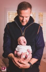 man looking down at baby yawning