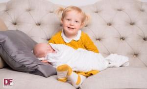 little girl on sofa holding baby