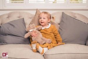 Little girl on sofa cuddling teddy bear
