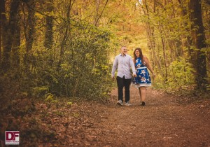 man and woman holding hands and walking through woods